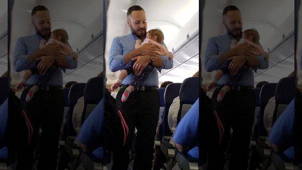 Steward uspokaja placzace niemowle